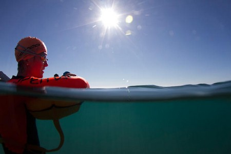 Swimmer resting on Orca swim buoy